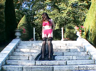 On the stone steps of an old estate in Europe, Anna Song appears, clad in a long, black leather coat over her sexy bra and panties.