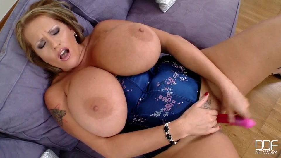She teases us with her cleavage in a satiny blue bustier, then lays on a couch, reveals her legendary 40f beauties.
