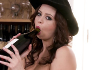 This time the bosomy czech is in a black dress, a cowboy hat as she looks through the bottles of wine on a dining room shelf.