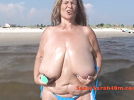 Sarah oils her huge tits at the seaside